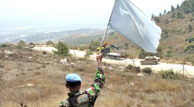 A UN soldier waves a UN flag at Israeli troops