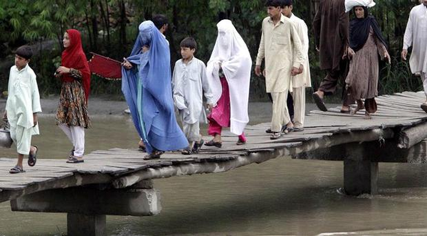 People use a make-shift bridge to flee their homes hit by heavy flooding in Peshawar. (AP)