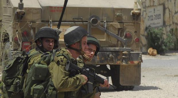 Israeli soldiers take position next to a military vehicle near the site of an exchange of fire between Israeli and Lebanese troops