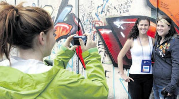 US-style peace camp comes to Belfast Juliette Candela (left) takes a photograph of her friends Frankie Giamona (centre) and Toni Giamona during a visit to the peace walls in west Belfast