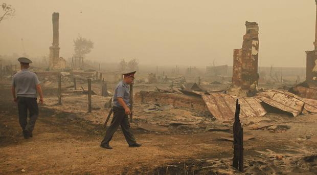 Two police officers near the ruins of houses destroyed by wildfires in Russia (AP)