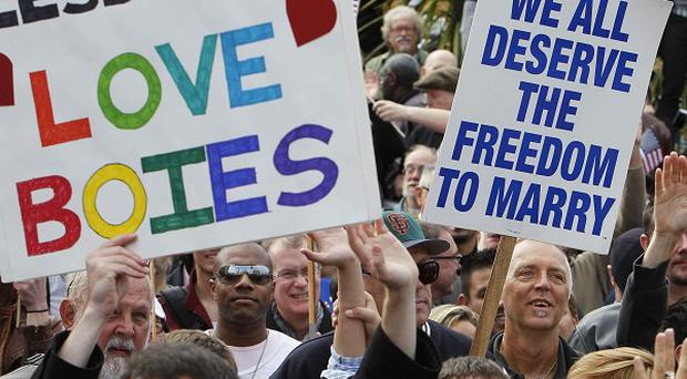 People attend a rally celebrating a federal judge's decision overturning California's same-sex marriage