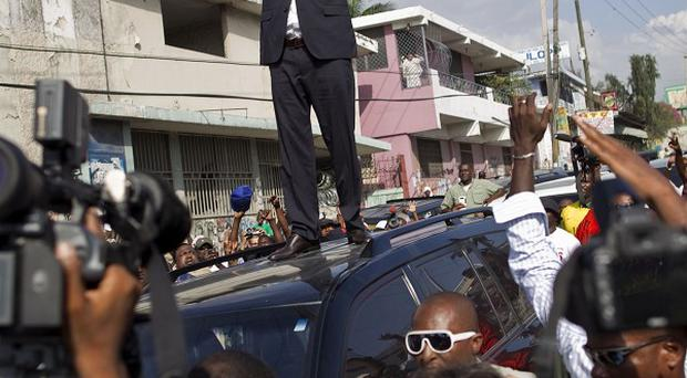 Wyclef Jean greets supporters from the top of a vehicle after submitting the paperwork to run for president of Haiti (AP)