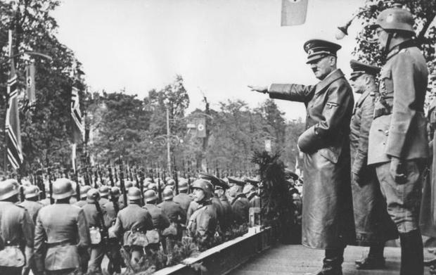 March 1938 file photo, Adolf Hitler, salutes German troops parading in Vienna, Austria.
