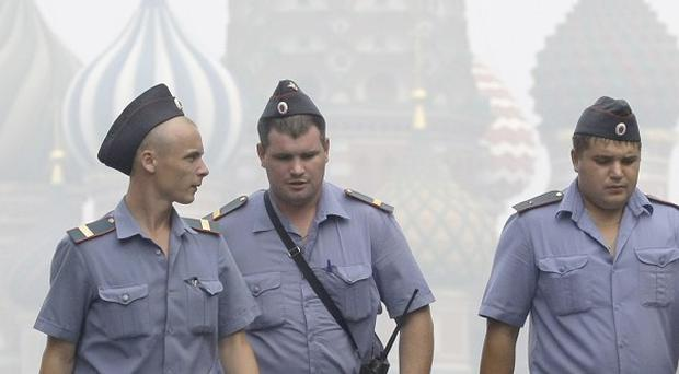 Police officers at Red Square with St Basil's Cathedral visible through the smog (AP)