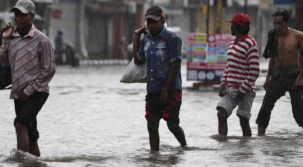People wade through a flooded street in rain in Jammu, India (AP)