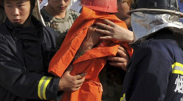 Rescuers escort a miner on to an ambulance at the site of a fire at Luoshan Gold Mine in Zhaoyuan (AP)