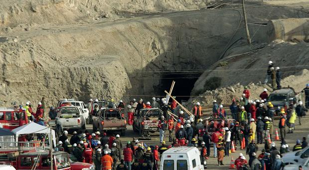 Relatives and rescue workers stand outside a collapsed mine in Chile (AP)