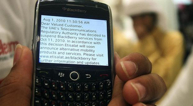 A BlackBerry user displays a text message sent by his service provider notifying him of the suspension of services at a mobile shop in Dubai (AP)