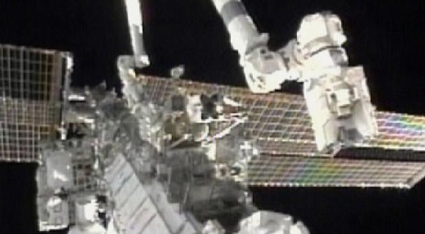Astronauts Douglas Wheelock, top, and Tracy Caldwell Dyson work on the International Space Station (AP)