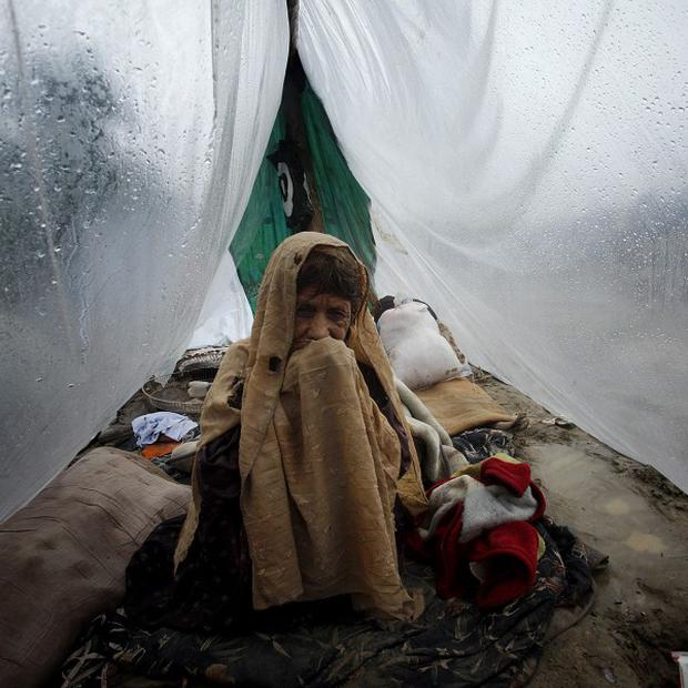A woman sits in a makeshift tent made from a plastic sheet as rain falls near Pabbi, north west Pakistan (AP)