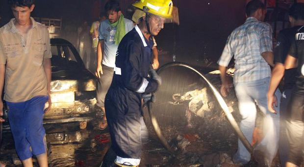 A firefighter works at the scene of an explosion in Basra (AP)