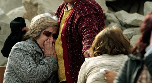 Relatives wait outside a collapsed mine where about 34 miners are trapped in Copiapo, Chile (AP)