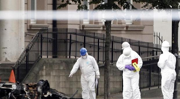 Forensic officers examine the scene where a car bomb exploded outside the Strand Road police station in 2010