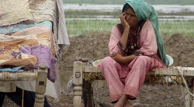 A woman takes shelter on higher ground due to flooding in an area of Jaffarabad, Pakistan (AP)