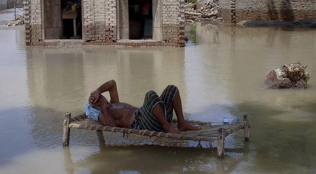 A Pakistani villager rests as his house is submerged by flood water in Ghazi Ghat, Pakistan (AP)