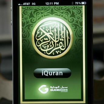 An iPhone displays an app called iQuran (AP)