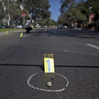 A bullet cartridge is circled in chalk on the street where a man was shot dead in Tijuana, Mexico