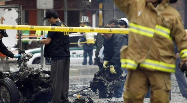 The police anti explosive unit inspects the wreckage of a car bomb in Bogota