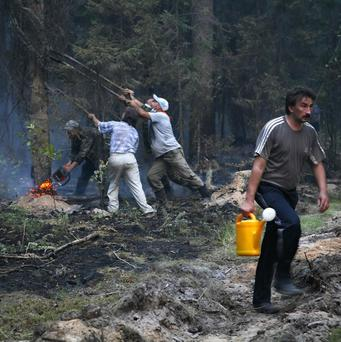 Volunteers try to extinguish a forest fire near the village of Kovrigino (AP)
