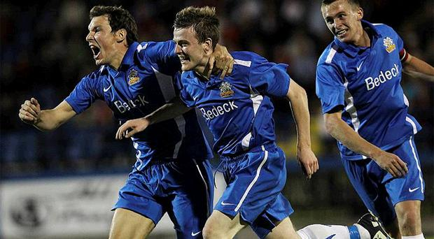 Glenavon's Jay Magee (left) and Kyle Neill (middle) celebrate with goalscorer Brendan Shannon