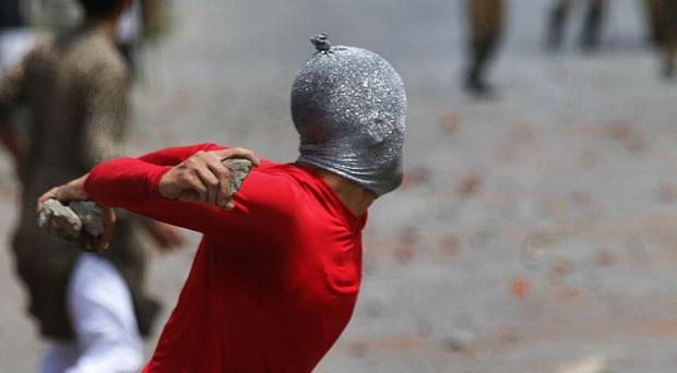 A Kashmiri Muslim protester throws stones at Indian paramilitary soldiers (AP Photo/Dar Yasin)