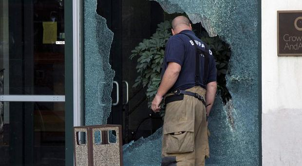 A firefighter looks into a shot-out window at the scene of a multiple fatal shooting near City Grill in Buffalo. (AP)