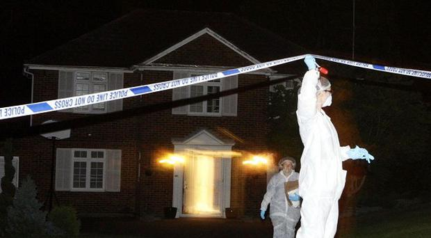 Officers at a house in Surrey where a a man in his 60s was found dead