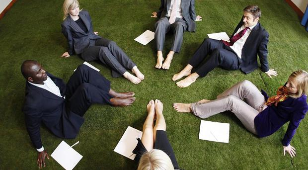 Business guests test out the new grass-turfed meeting room at Crowne Plaza London Docklands