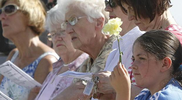 Relatives pay tribute during the 12th anniversary service at the Omagh memorial garden