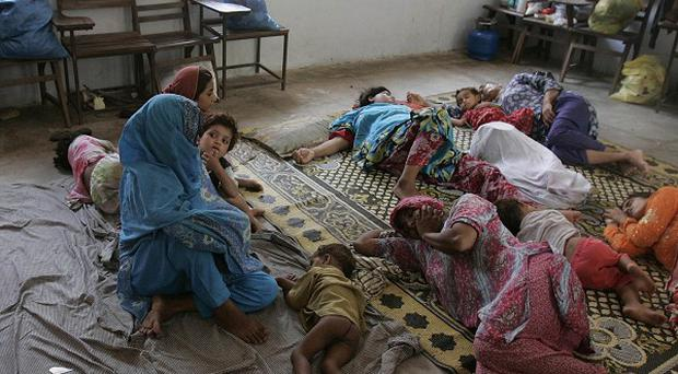 Flood survivors rest inside a school building converted into a temporary camp for displaced people in Multan, Pakistan (AP)