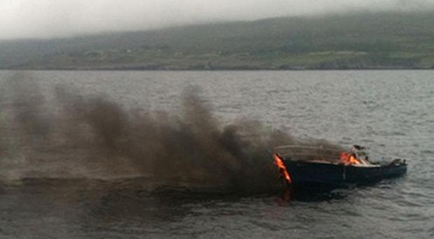 A 25ft motor cruiser on fire in Bantry Bay, near Adrigole harbour, in which three people were killed off the coast of Co Cork