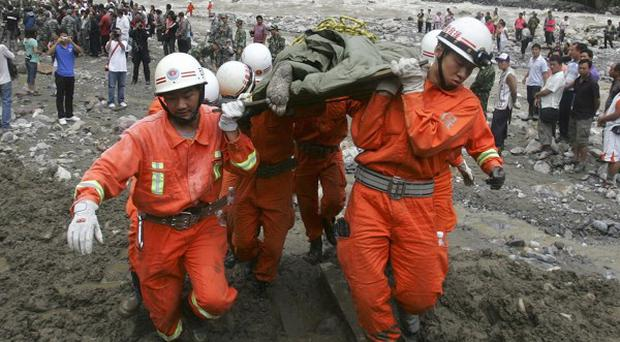 Rescuers move a victim's body after a landslide in Gongshan county, in south-west China's Yunnan province (AP)