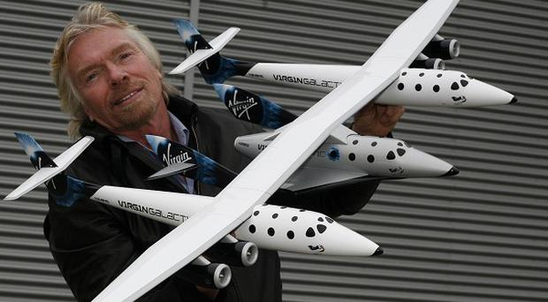 Virgin boss Sir Richard Branson with a model of Virgin Galactic's space tourism jet