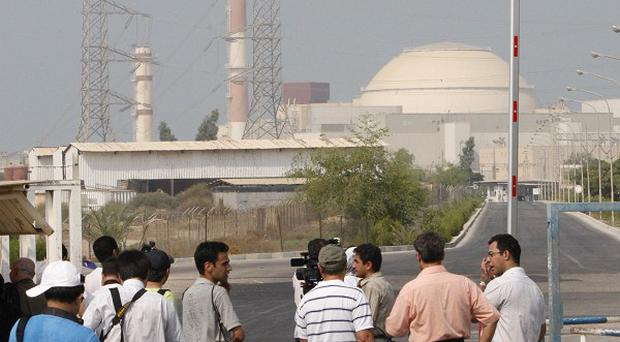 Media stand near the Bushehr nuclear power plant with its reactor building in the background