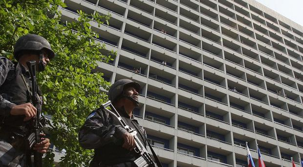 Police stand guard at the Intercontinental Hotel after it was invaded by gunmen who took hostages (AP)