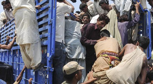 Pakistan flood-affected swarm to get relief food distributed by a local charity group in Baseera, central Pakistan (AP)