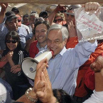 Chile's President Sebastian Pinera holds a plastic bag containing a message from miners trapped in a collapsed mine