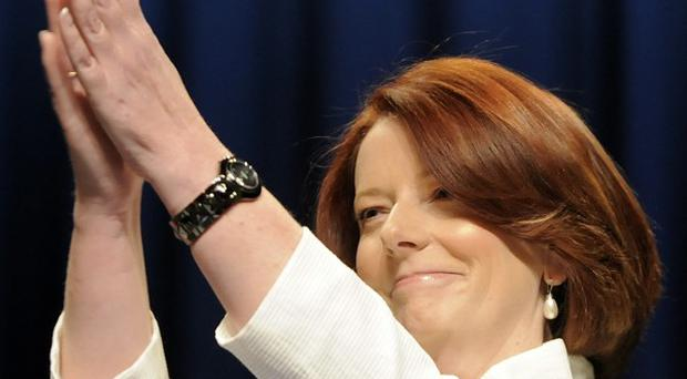 Australian Prime Minister Julia Gillard salutes wellwishers at the end of voting in Melbourne (AP)