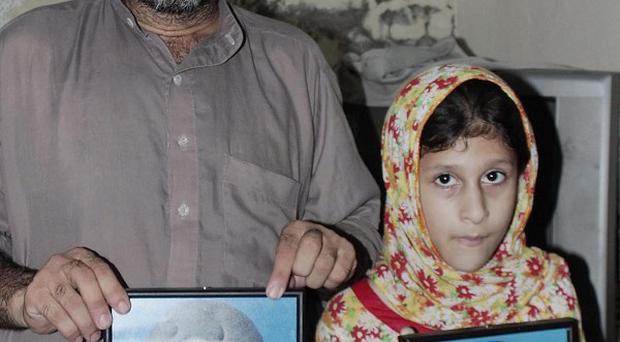 The pictures of two brothers, Moiz Butt, left, and Muneeb Butt, who were killed by a mob in Pakistan, displayed by their father Sajjad and sister Momina