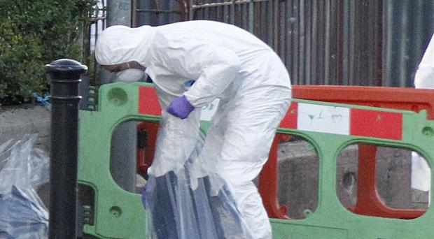 Forensic officers remove evidence from the scene of a bomb explosion in Lurgan
