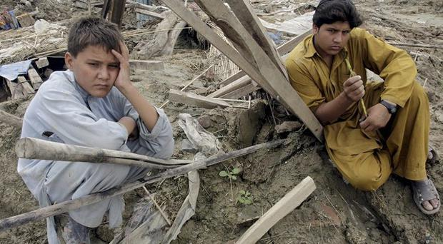 Pakistani villagers near their ruined houses in Nowshera (AP)