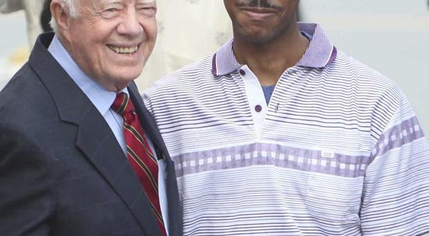 Former US president Jimmy Carter and Aijalon Gomes prepare to leave North Korea