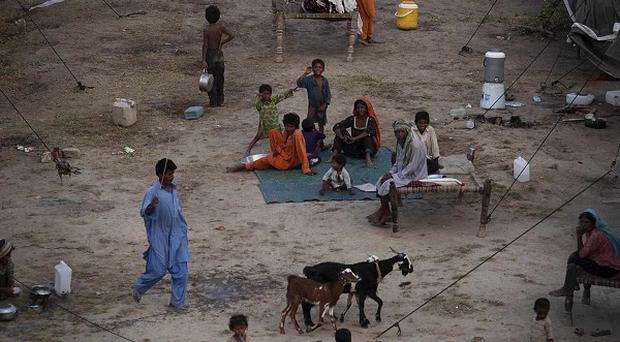 Pakistanis displaced by flooding sit outside tents at a temporary camp (AP Photo)