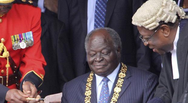 Kenyan President Mwai Kibaki prepares to sign the new constitution into law (AP)