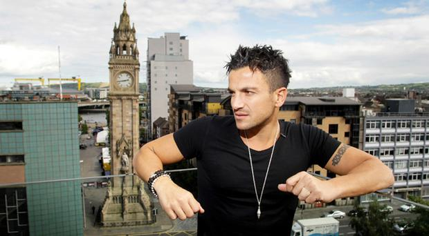 Peter Andre on the balcony of Belfast's Merchant Hotel with the Albert Clock behind