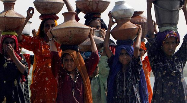 Pakistani flood survivors, holding empty containers on their heads, walk in search of clean water (AP)
