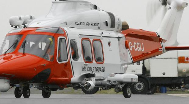 A paraglider has died after falling 150ft near cliffs, the Coastguard said