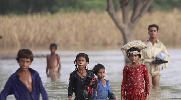 Pakistani children living on patches of land surrounded by floodwaters wade along a road (AP)