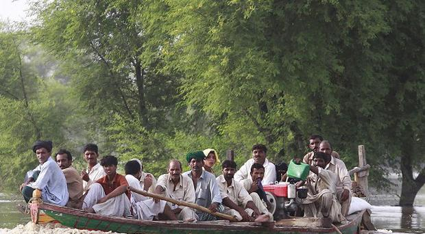 Pakistanis living on patches of land surrounded by floodwaters are ferried on a boat (AP)